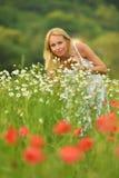 La femme heureuse enceinte dans un pavot fleurissant mettent en place dehors Photographie stock libre de droits
