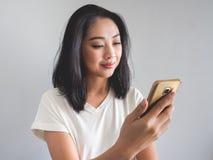La femme heureuse est smartphone émouvant photographie stock libre de droits