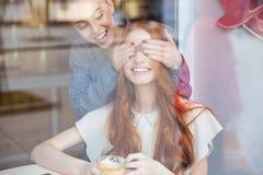 La femme heureuse a fermé des yeux à son ami féminin en café Images libres de droits