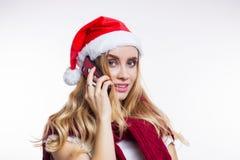 La femme heureuse gaie met dessus le chapeau rouge et les entretiens de Santa sur son smartphone Achats en ligne, remises de Noël photo stock