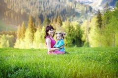 La femme heureuse joue avec l'enfant sur un sommet de montagne Le concept de Images stock