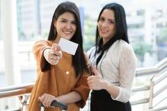 La femme heureuse montrant des paniers de carte de crédit et de prise voyagent images libres de droits