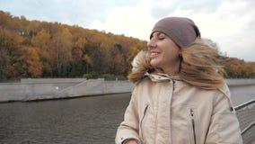 La femme heureuse a plaisir à flotter sur le bateau de visite sur la rivière dans la ville à l'automne coloré banque de vidéos