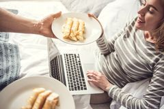 La femme heureuse reçoit le petit déjeuner dans le lit photo libre de droits