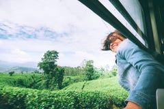 La femme heureuse regarde de la fenêtre de train pendant le déplacement dessus plus images stock