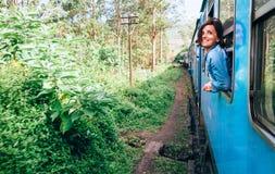 La femme heureuse regarde de la fenêtre de train pendant le déplacement dessus plus photographie stock