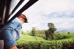 La femme heureuse regarde de la fenêtre de train pendant le déplacement dessus plus image stock