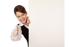 La femme heureuse retient le panneau-réclame et affiche le pouce photos stock
