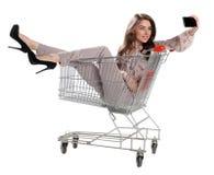 La femme heureuse s'asseyant dans le chariot à achats et se font la photo Photographie stock
