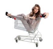 La femme heureuse s'asseyant dans le chariot à achats et se font la photo Photos libres de droits