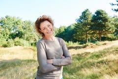 La femme heureuse se tenant avec des bras a croisé en parc photo libre de droits
