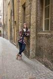 La femme heureuse se tient dans une allée dans la ville historique Image stock