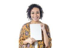 La femme heureuse sourit et tient une carte pour l'espace publicitaire Photographie stock