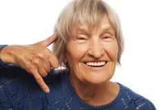 La femme heureuse supérieure me fait à un appel geste Photo stock