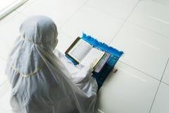 La femme inconnue lit le Quran avec un bâton d'indicateur image stock