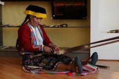 La femme indigène péruvienne tisse un tapis photos stock