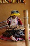 La femme indigène péruvienne tisse un tapis photo stock