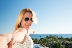 La femme indique avec son doigt la mer d'un balkony dans des vacances d'été Photo stock