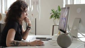 La femme informelle avec un tatouage travaille avec une table d'ordinateur