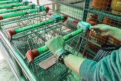 La femme insère la pièce de monnaie au chariot à supermarché photographie stock