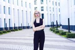 La femme intelligente a plié ses bras sur le fond du centre d'affaires Photos libres de droits