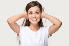 La femme irritée a fermé ses oreilles avec le tir de studio de mains images stock