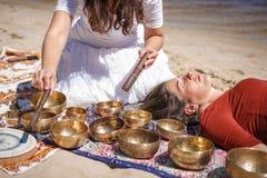 La femme jouant un chant roule également connu en tant que cuvettes de chant de Tibétain, cuvettes de l'Himalaya Fabrication du m Photo libre de droits