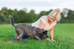 La femme joue avec un chien hybride de terrier sur un pré Photo stock