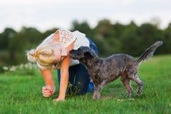 La femme joue avec un chien hybride de terrier sur un pré Photographie stock