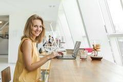 La femme joyeuse boit le café et le travail photos stock