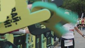 La femme joyeuse donne des fives de taille à la foule encourageante sur des mains de mousse au marathon clips vidéos