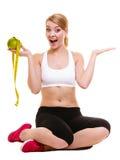 La femme joyeuse tient le pamplemousse et la bande de mesure images stock