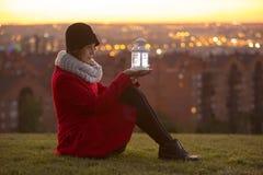 La femme l'hiver vêtx tenir une lanterne menée de lumières Photographie stock libre de droits