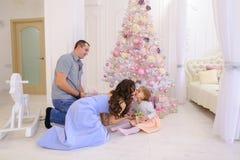 La femme, l'homme et la petite fille remettent à des cadeaux de Noël sa moitié dans s image stock