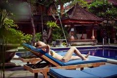 La femme la prenant un bain de soleil près d'une piscine Image libre de droits