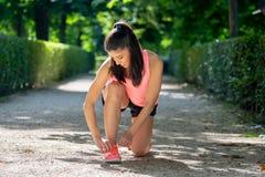 La femme latine attirante de coureur de sport attachant son espadrille de chaussure lace en parc Images stock