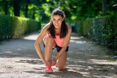 La femme latine attirante de coureur de sport attachant son espadrille de chaussure lace en parc Photographie stock
