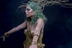 La femme latine avec le diadème vert de cheveux et d'or, porte une guerre faite main Photographie stock libre de droits