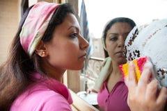 La femme lave une fenêtre de miroir Image stock