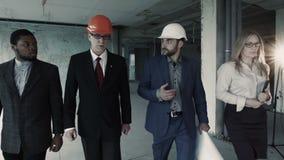 La femme, les hommes dans le costume et le casque marchent, discutent, communiquent La femelle avec le comprimé est le Directeur  banque de vidéos
