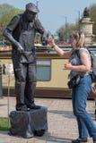 La femme lie nerveusement des doigts avec la statue vivante Image libre de droits