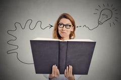 La femme lisant un livre énorme a une bonne idée image libre de droits