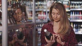 La femme lit le label de la bouteille de champagne au magasin du marché et le sourire a perdu dans les pensées au sujet de la fut banque de vidéos