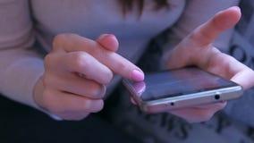 La femme lit le livre sur le smartphone renversant des pages par le doigt, plan rapproché de mains banque de vidéos