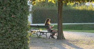 La femme lit le reder électronique en parc sur le banc banque de vidéos