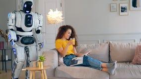 La femme lit un magazine tandis qu'un droid apporte son jus Cyborg et concept humain clips vidéos