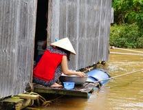 La femme locale prépare le repas sur son bateau images libres de droits