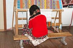 La femme locale tisse un tapis à la main à Antalya, Turquie Photos stock