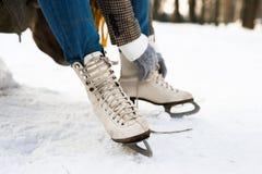 La femme méconnaissable en hiver vêtx la mise sur de vieux patins de glace Photo stock