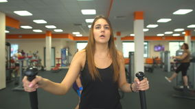 La femme méconnaissable mince marche entraîneur elliptique d'isolement et sourire banque de vidéos